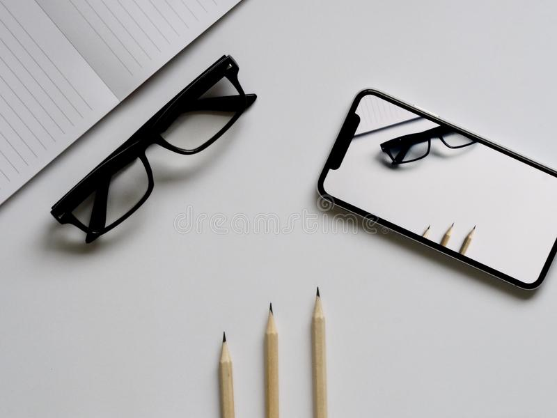 Three Pencils, Eyeglasses, and Smartphone on White Table stock image