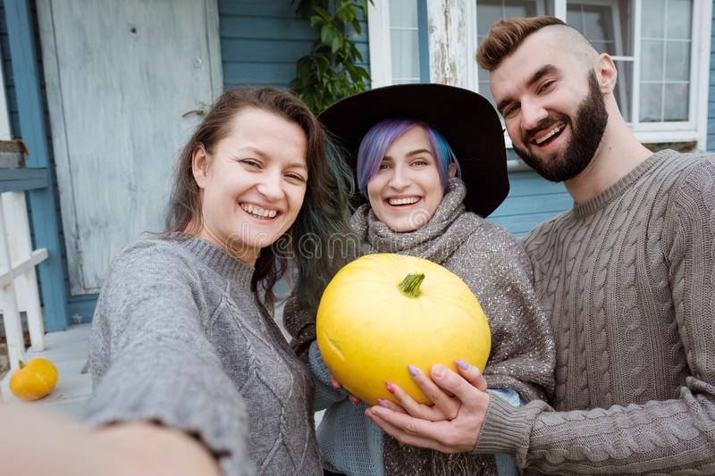 Three people in background of village house on farm talk and laugh. Take pictures of themselves against the background royalty free stock photography