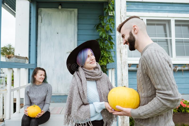 Three people in background of village house on farm talk and laugh. royalty free stock photo