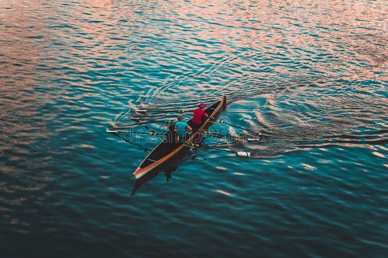 Three People on Brown Canoe Sailing on Calm Water stock photo