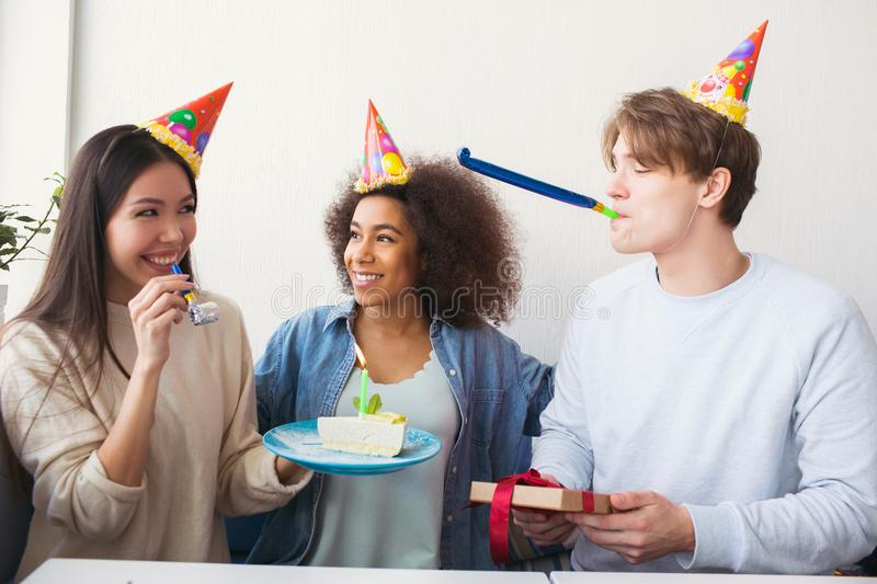 Three people are celebrating birthday. They wears funny hats. Girl is holding a plate with cake while guy has a present stock photos