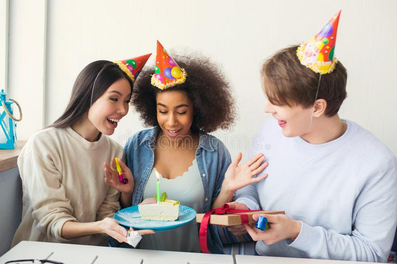 Three people are celebrating birthday. They wears funny hats. Girl is holding a plate with cake while guy has a present stock image