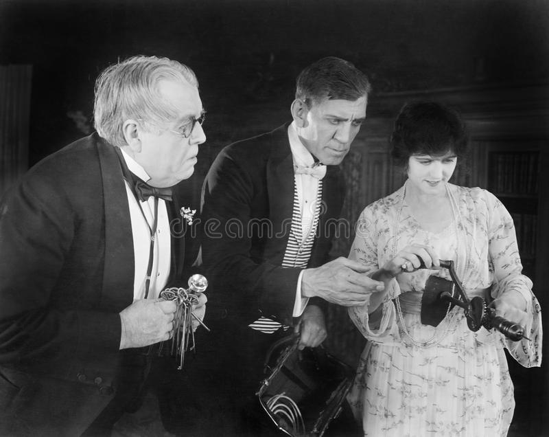 Three people checking out a manual drill. (All persons depicted are no longer living and no estate exists. Supplier grants that there will be no model release stock photos