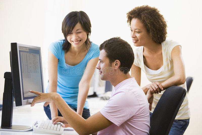 Three people on computer. Three people in computer room pointing at monitor and smiling