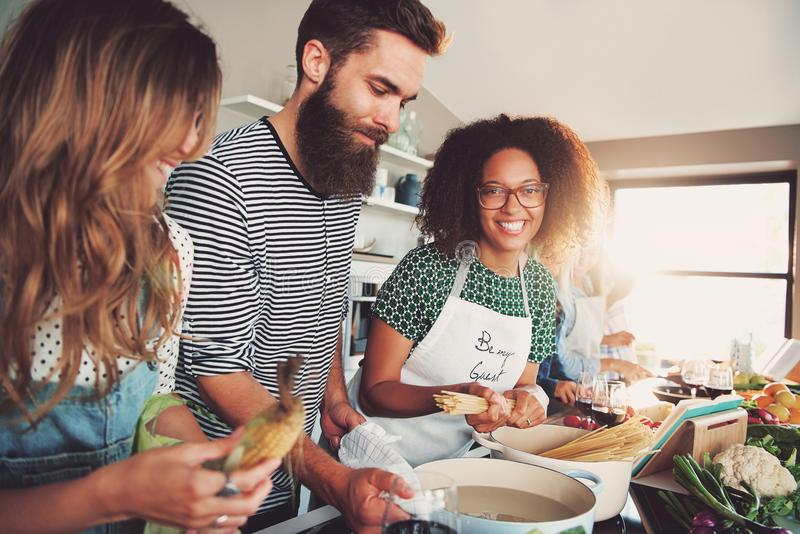 Three people cooking at kitchen stock images