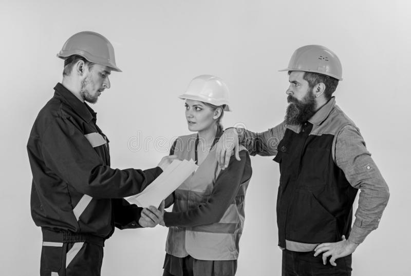 Three people discussing over plan, builders, engineers royalty free stock photography