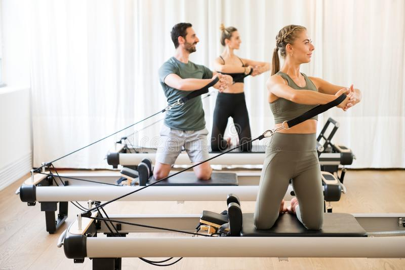 Three people exercising torson rotation at gym stock photo
