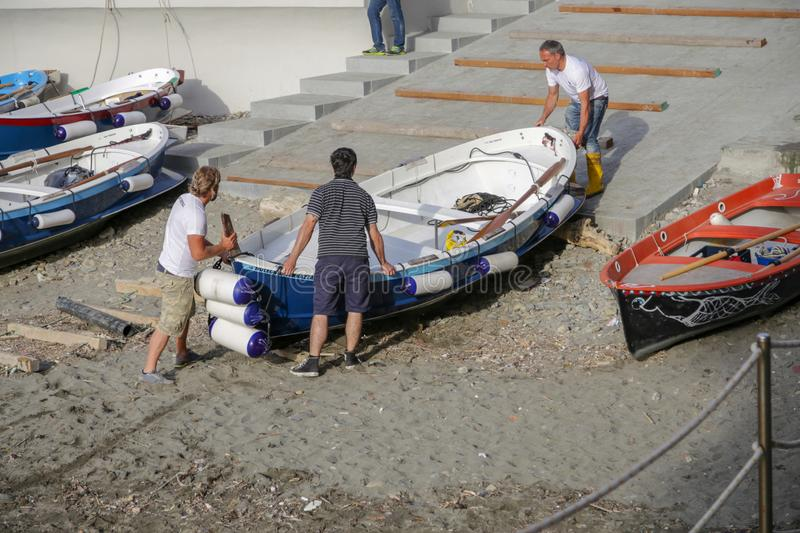Three people fishermen carry out the boat, vernazza, Cinque Terre, Liguria, Italy stock photo