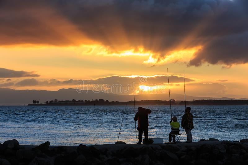 People fishing at sundown, with sunbeams through the clouds stock image