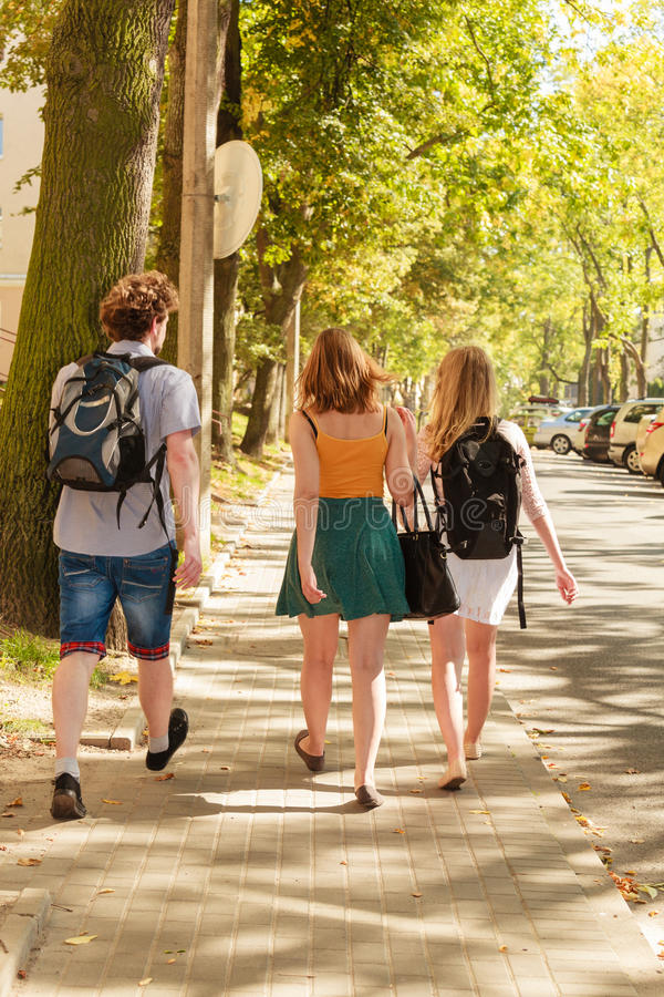 Three people friends walking outdoor. stock photo
