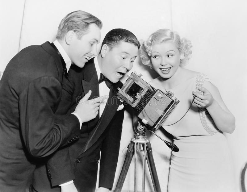 Three people looking through a camera and laughing. (All persons depicted are no longer living and no estate exists. Supplier grants that there will be no model royalty free stock photography