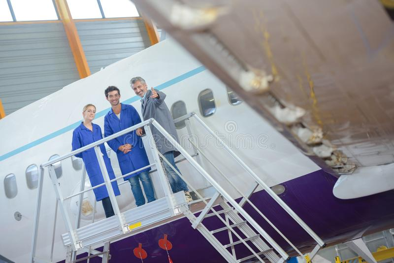 Three people on platform next to aircraft stock photography