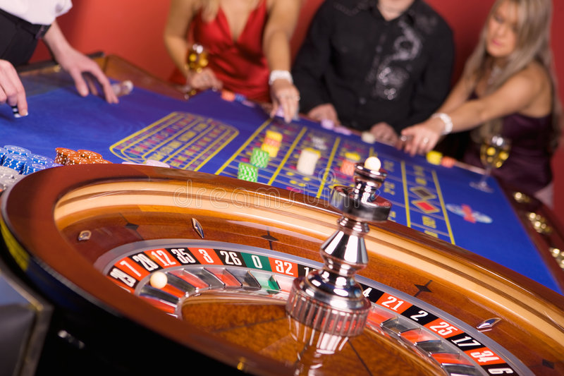 Three people playing roulette. Chips on blue casino table stock image