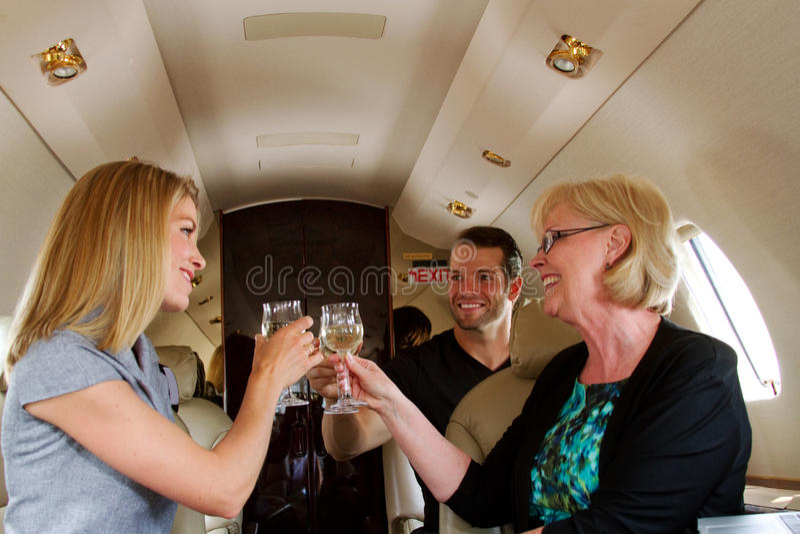Three people proposing toast. Three people on jet proposing toast stock images