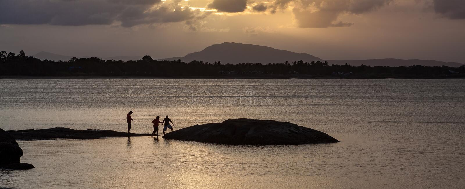 People silhoutted on Queens Beach rocks, Bowen stock photos