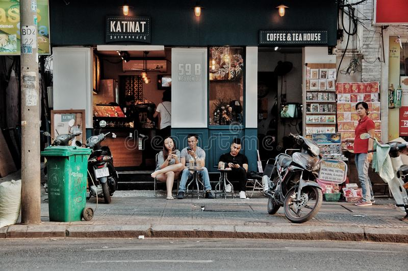 Three People Sitting on Chairs Outside Coffee & Tea House Near Motorcycles royalty free stock images