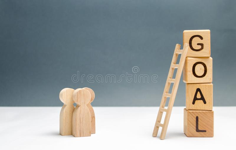 Three people are standing near the tower of cubes with the word goal. Business concept. cooperation and teamwork. Evaluation. Of options and means to conquer stock images
