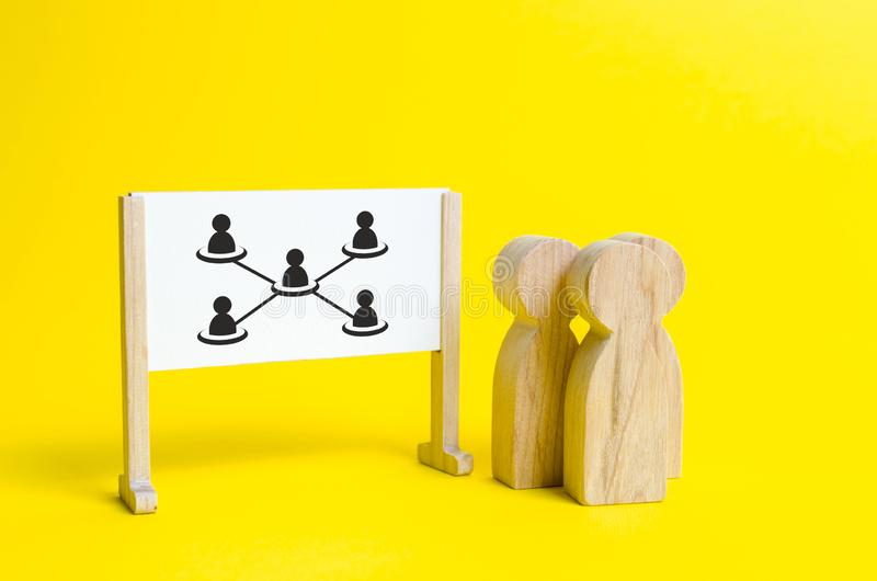 Three people are standing near the white board with the image of the hierarchy of employees in the company. Concept of business royalty free stock image