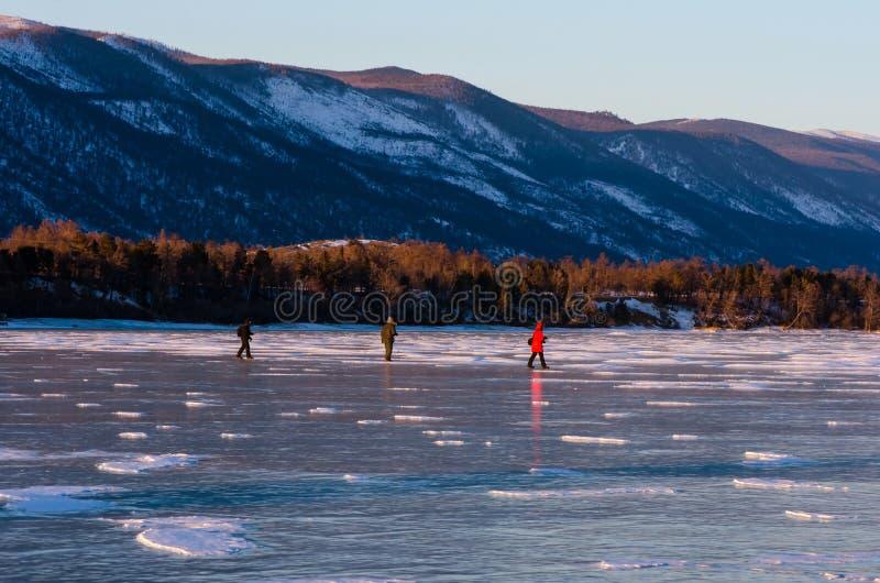 Three people walking on cracked ice of a frozen lake Baikal royalty free stock image