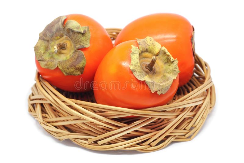 Three Persimmons In a Wicker Bowl Isolated On White stock photos