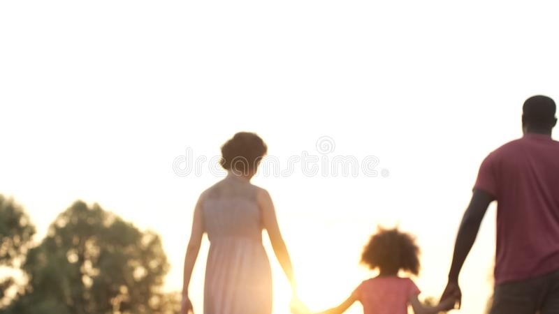 Three person family walking into sunset, happy future together, memories royalty free stock photography