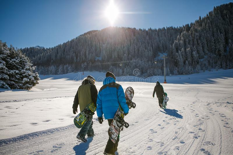 Three Person Holding Bubble Jacket Carrying Snowboards stock image