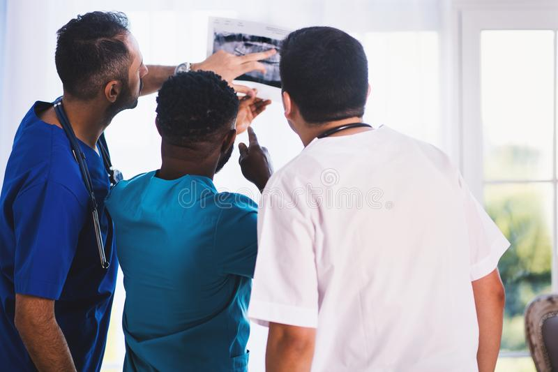 Three Person Looking at X-ray Result royalty free stock photography