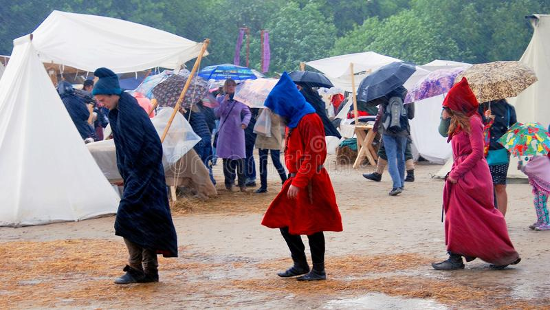 Three persons walk under the rain. They are reenactors and they are dressed like medieval people, they do not carry any umbrellas. It's raining heavily, and at