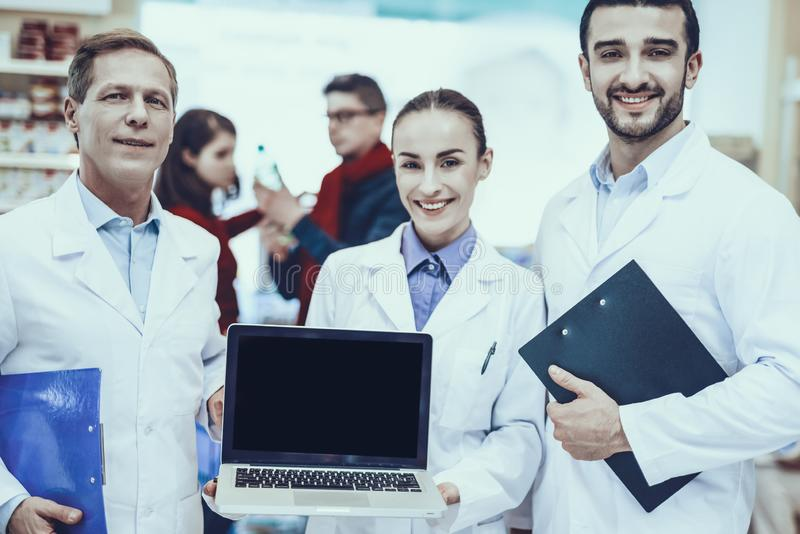 Pharmacists Posing with Laptop. Three Pharmacists Posing and Smiling. Pharmacists is a Caucasian Men and Young Woman. Woman Holding a Laptop. Customers Choose a stock photo
