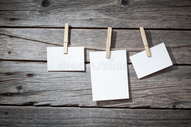 Three photo paper attach to rope with clothes. Pins on wooden background stock photo