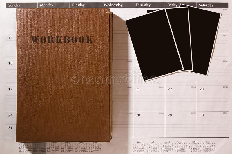 Tattered workbook with photos. Three photos on an office calendar with an old tattered workbook stock image