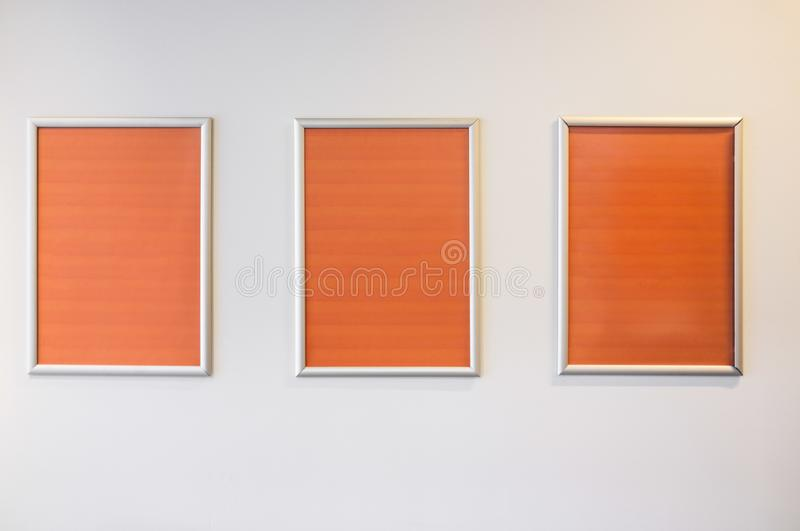 Three picture frames hanging on white wall. royalty free stock photo