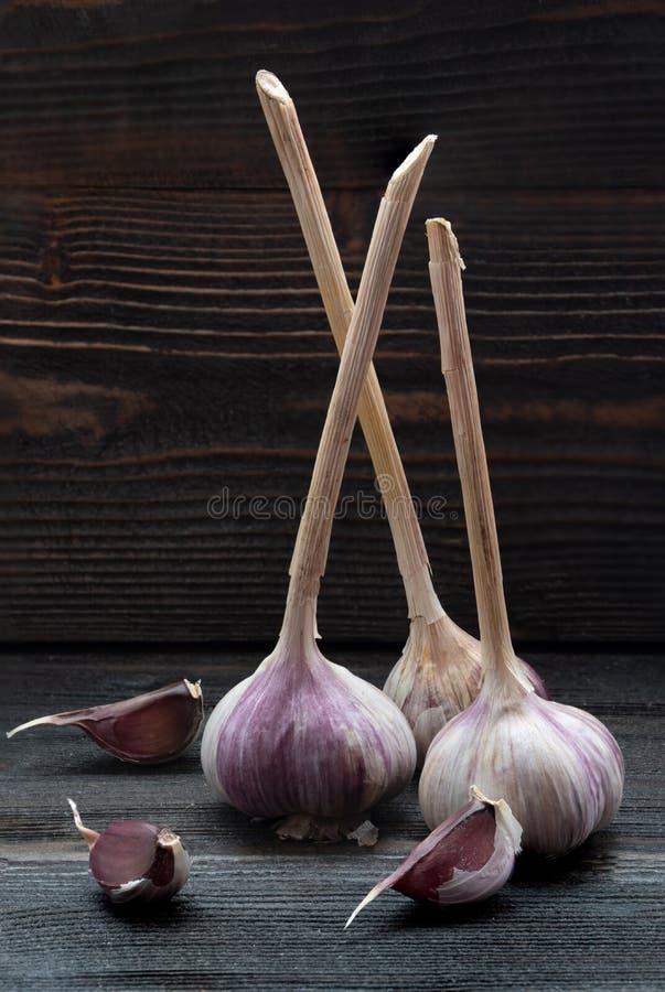 Three pieces of garlic on dark wooden desk surface stock photos