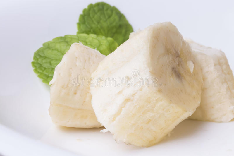 Three pieces of sweet sliced banana with mint leaves stock photography