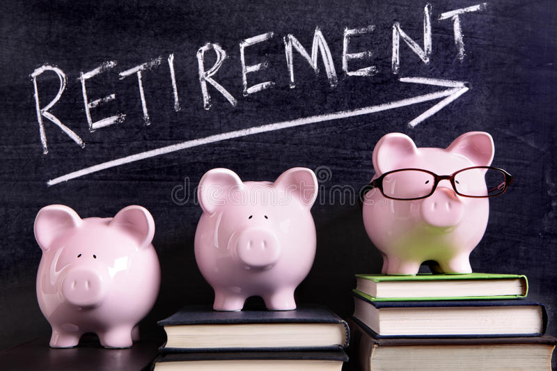 Three piggy banks with retirement savings plan. Three pink piggy banks standing on books next to a blackboard with retirement savings message. Sharp focus on the stock photography