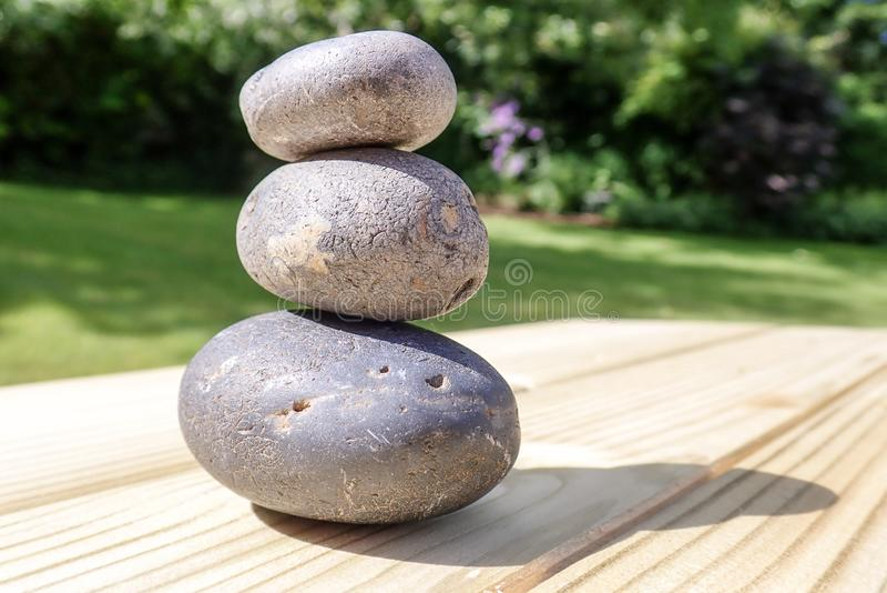 Three piled stones on pine wood surface stock photos