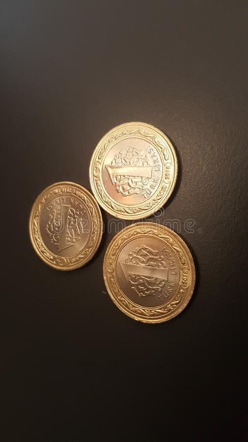 Three 1 Turkish Lira coins arranged in a triangular geometry with some slight perspective in close up image with black matte backg stock photo