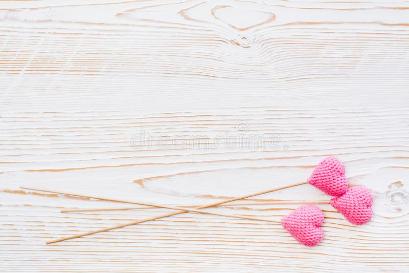 Three pink knitted hearts on sticks on a white wooden background stock image