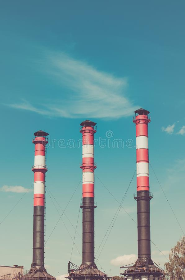 Three pipes of the plant against the background of the blue sky royalty free stock photo