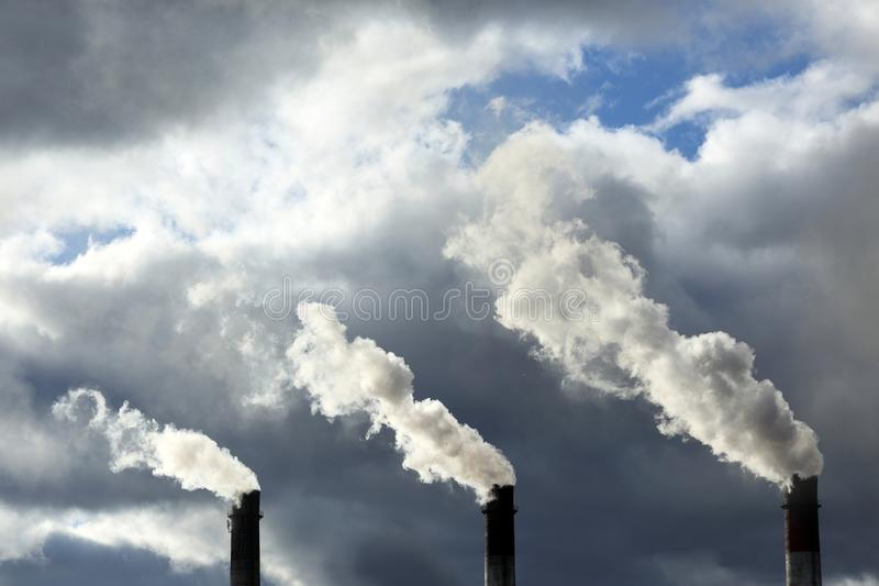 Three pipes with smoke against the background of a beautiful sky stock image