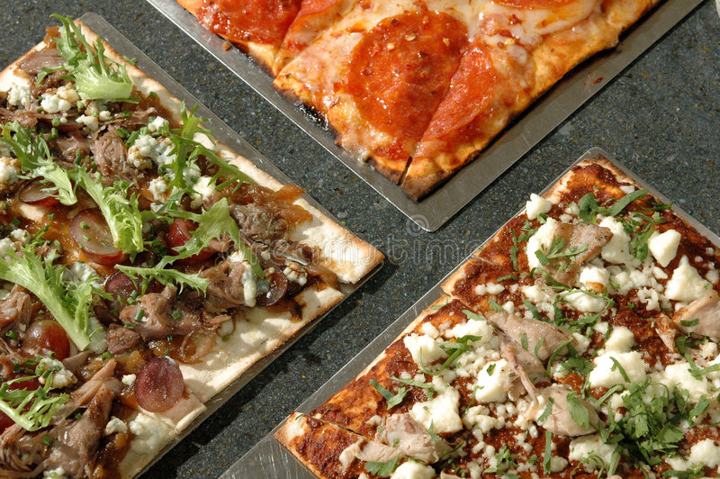 Three pizzas. Three square thin crust pizzas royalty free stock image
