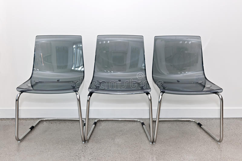 Three plastic chairs against wall stock image