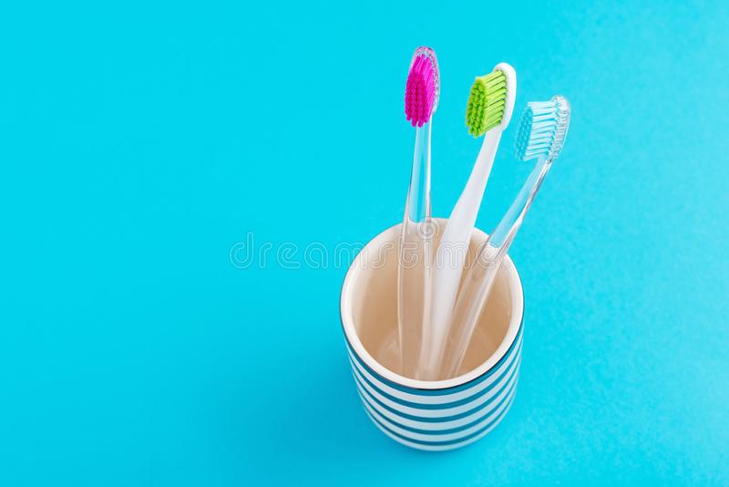 Three plastic colorful toothbrushes in glass on a blue background, close up royalty free stock photos