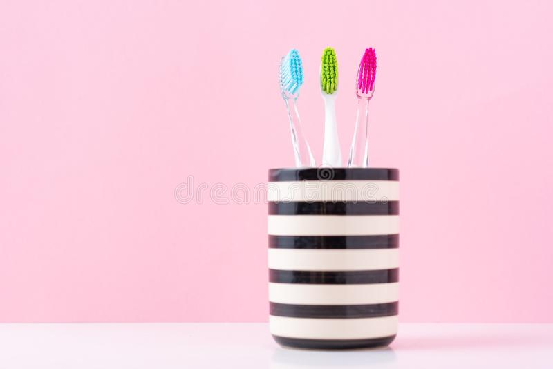 Three plastic colorful toothbrushes in glass on a pink background, close up royalty free stock photos