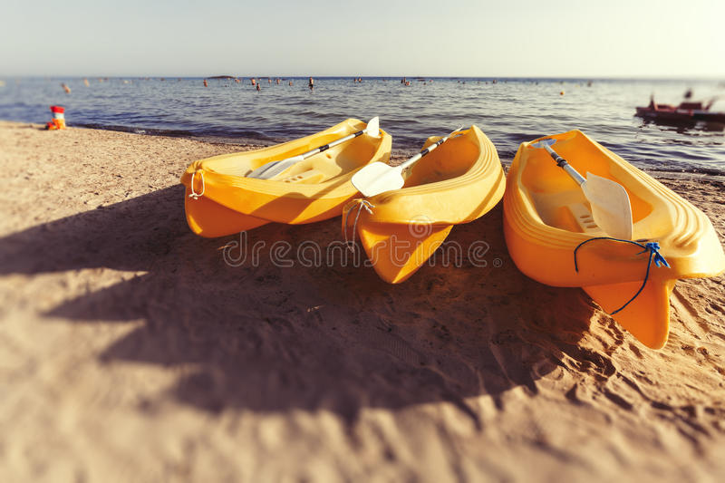 Three plastic yellow canoe on the beach at Sea. Summer. Three yellow canoes are on the beach. In the background the Mediterranean Sea with a few people in the royalty free stock image