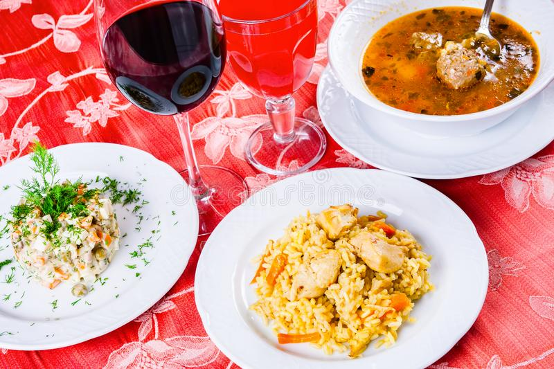 Three plates with lunch dishes on table. Salad, soup with meatballs and pilaf stock photography