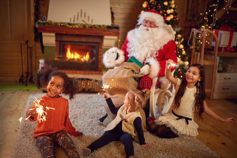 Three playful girls with Santa Claus in Christmas atmosphere. Three girls playing with Christmas sprinklers with Santa Claus in Christmas atmosphere royalty free stock images