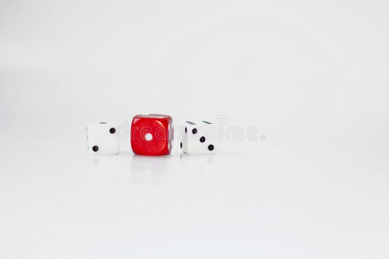 Three playing dice with a shiny white background, the red central one faces the camera while the others two and three stock photography