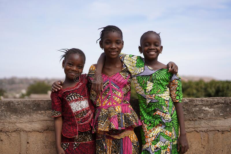 Three Pleasant African Girls Posing For A Panorama Picture On a Bridge. Candid photo of real African children in a natural village environment stock image