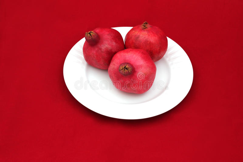 Three pomegranates on a white plate - symbol of Jewish new year. Pomegranates are traditional symbol of Jewish new year symbolizing many good deeds as the seeds royalty free stock image